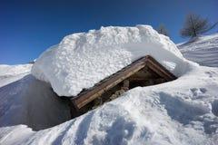 Bergplattelandshuisje met sneeuw wordt behandeld die. Royalty-vrije Stock Afbeelding