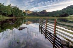Bergreflexioner i sjön med staketet Fotografering för Bildbyråer