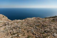 Bergrichel met overzees en horizon op achtergrond voor productplaatsing Rotsrand en steil met blauw water  Stock Foto