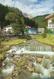 Bergrivier die door dorp vloeien Stock Afbeelding
