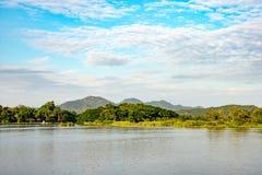 Bergrivier met blauwe hemel en wolkenachtergrond Stock Afbeeldingen