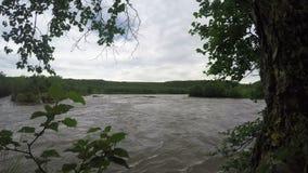 Bergrivier met modderig water in somber bewolkt weer stock footage