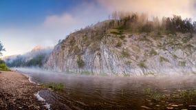 Bergrivier onder rotsmuren in mist Royalty-vrije Stock Afbeeldingen
