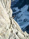 Bergsbestigare på en brant klättrarutt i de franska fjällängarna i Chamonix royaltyfri bild