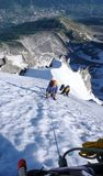 Bergsbestigare på en brant klättrarutt i de franska fjällängarna i Chamonix royaltyfri fotografi