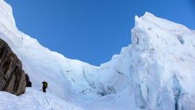 Bergsbestigare som heading upp en brant hängande glaicer runt om seracs i fjällängarna av Schweiz royaltyfria foton
