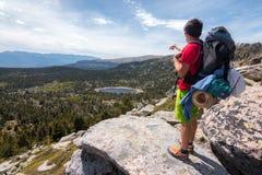 Bergsbestigare som pekar en mycket liten sjö Arkivbilder