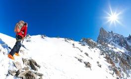 Bergsbestigaren klättrar ett snöig maximum I bakgrund den berömda maximala bucklan du Geant i Mont Blanc Massif, den högsta europ Royaltyfri Bild