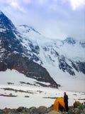 Bergsbestigaren står på tältet på foten av etttäckt berg Begrepp av loppet och extrem avkoppling royaltyfri fotografi