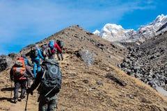 Bergsbestigningexpeditionflyttning in mot berget för hög höjd Arkivfoton