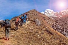 Bergsbestigningexpeditionflyttning in mot bergsolsken för hög höjd Royaltyfri Fotografi