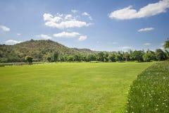 Bergsikt för grönt gräs med bakgrund för blå himmel arkivfoton