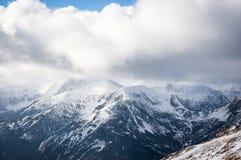 Bergsikt i solljus med moln Royaltyfria Foton