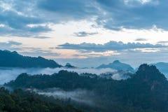 Bergsikt med den dimmiga miljön under soluppgång Fotografering för Bildbyråer