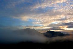 Bergsikt runt om dimman Arkivfoto
