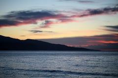 Bergsilhouet in overzees na zonsondergang Stock Foto's