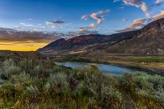 Bergskedja, flod och solnedgång Arkivfoton