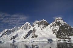 Bergskedja på ön nära den soliga antarktiska halvön Arkivbilder