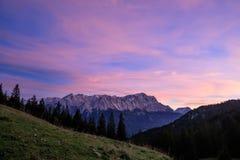 Bergskedja, skog och äng på solnedgången arkivbild