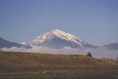 Bergskedja som täckas i snö, och dimma med ängen sluttar Royaltyfri Bild