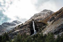 Bergsnö och glaciär i Schweiz med vattenfallet royaltyfri fotografi