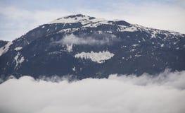 Bergspitze über Wolken Stockfotos