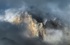 Bergspitze, die durch Wolken im Kaukasus späht stockbilder
