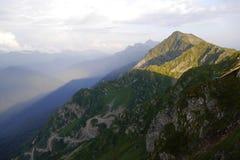 Bergspitze, die einen Schatten bei Sonnenuntergang in Rosa Khutor wirft Stockfotos