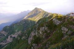 Bergspitze, die einen Schatten bei Sonnenuntergang wirft Rosa Khutor, Russland Lizenzfreie Stockfotos