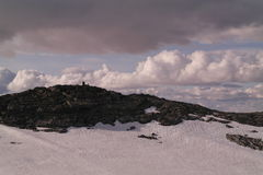 Bergspitze mit einem Steinsteinhaufen Stockfotografie
