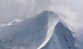 Bergspitze umfasst im Schnee- und Wolkennebel Lizenzfreie Stockfotografie
