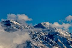 Bergspitzen über den Wolken mit Schnee stockfoto