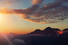 Bergspitzen in den Wolken, Sonnenuntergang Stockfotos