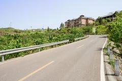 Bergssida guardrailed countryroad på solig vårdag Royaltyfria Bilder