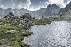 Bergsteigen durch den Gebirgssee unter felsigen Spitzen und Wolken stockbilder