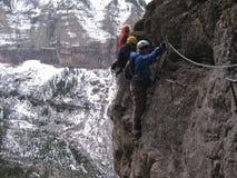 Bergsteiger überqueren entlang über Ferrata stockbilder