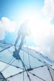 Bergsteiger auf einem Wolkenkratzer Stockbild