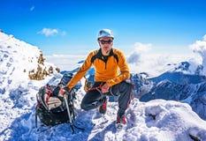 Bergsteiger auf einer Gebirgsspitzenaufstellung auf dem Hintergrund von schneebedeckten Bergen Lizenzfreies Stockfoto
