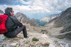 Bergsteiger, der auf dem Felsen bewundert das Bergpanorama sitzt Stockbild