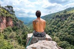 Bergsteiger, der auf die Oberseite sitzt stockfotos