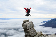 Bergsteiger, der auf Gipfel springt lizenzfreie stockfotografie