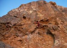 Bergsteiger, der die Spitze erreicht stockfotografie