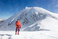 Bergsteiger, der in einer geschneiten Landschaft mit einem hohe Spitze behi steht stockbild
