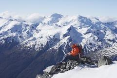 Bergsteiger, der Laptop auf Bergspitze verwendet Stockbild