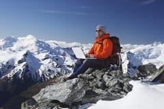 Bergsteiger, der Laptop auf Bergspitze verwendet Lizenzfreie Stockfotografie