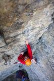 Bergsteiger in einem Sturzhelm klettert oben stockfotografie