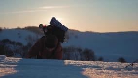 Bergsteiger erreicht die Spitze eines schneebedeckten Berges Ein Bergsteiger mit Rucksack klettert oben eine schneebedeckte Steig stock video footage