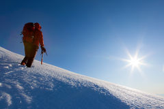 Bergsteiger geht auf einen Gletscher Wintersaison, klarer Himmel Stockfotografie