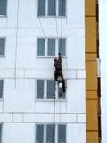 Bergsteiger gibt Reparaturarbeit für eine mehrstöckige Gebäudehöhe aus Stockfotos
