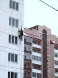 Bergsteiger gibt Reparaturarbeit für eine mehrstöckige Gebäudehöhe aus Stockbild
